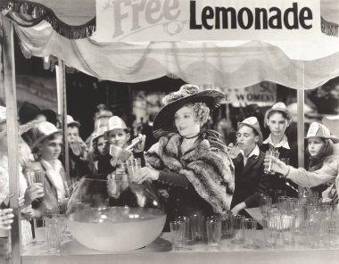woman distributing free lemonade