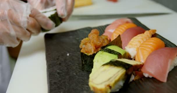 Detail mužské šéfkuchaře uspořádání sushi v zásobníku v kuchyni 4k