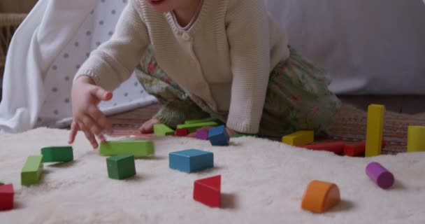 Front view of a Caucasian toddler enjoying time at home, sitting on a floor in a sitting room by a tent, playing with wooden blocks, slow motion