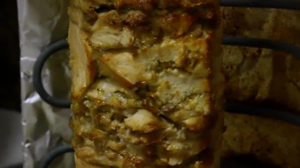 A csirke húsa nyárson forog, hogy előkészítse a shawarmát. Főzőcsirke a forgó asztalon.