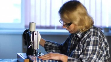 Shoot of woman sews on old sewing machine at home