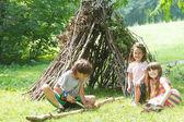Fotografia bambini che giocano vicino alla casa di bastone di legno
