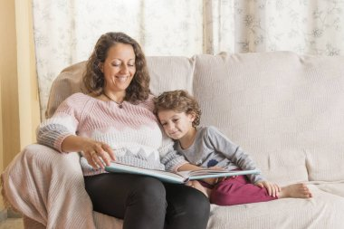 Child and a woman sitting on sofa reading a book.
