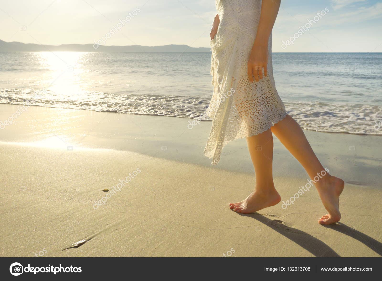 Mujer joven con vestido blanco caminando solo en playa