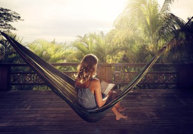 woman in a dress reading book in a hammock in the jungle at suns