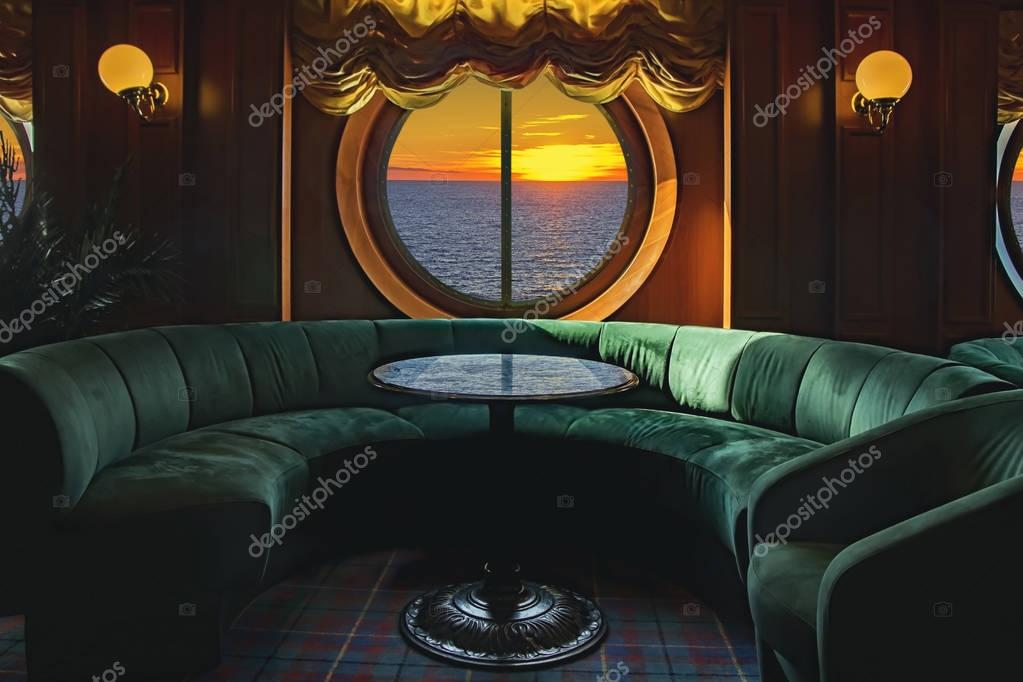 Lounge on a cruise ship, with tables and armchair in the sunset