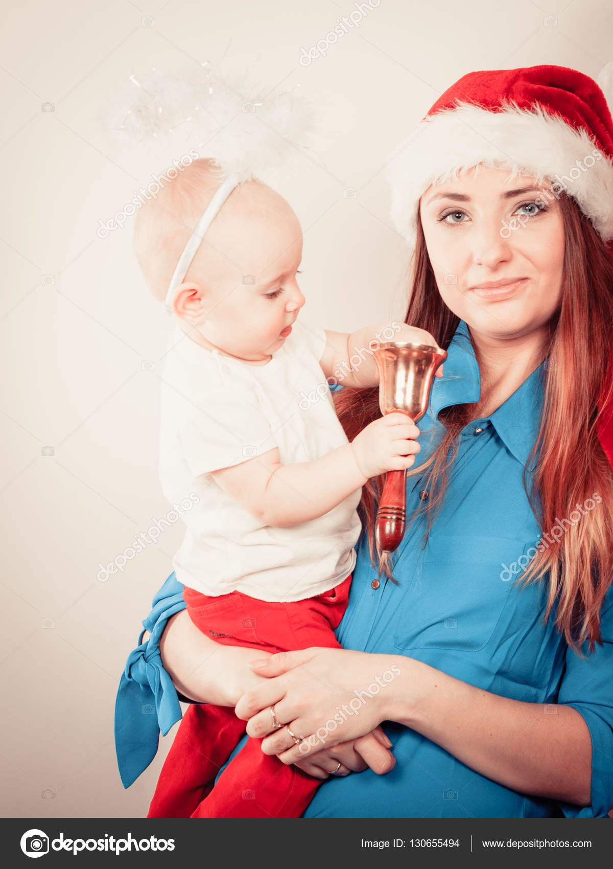 c3be4611b0690 Family celebration concept. Christmas woman with cute baby. Beautiful lady  has red santa claus cap.