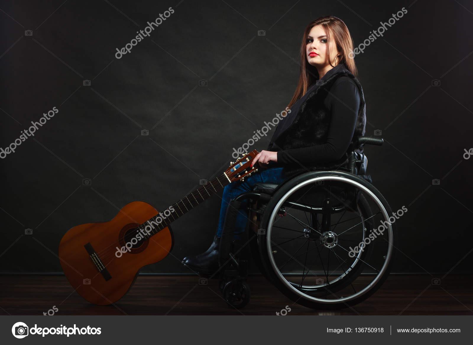 Sad disabled girl with guitar stock photo