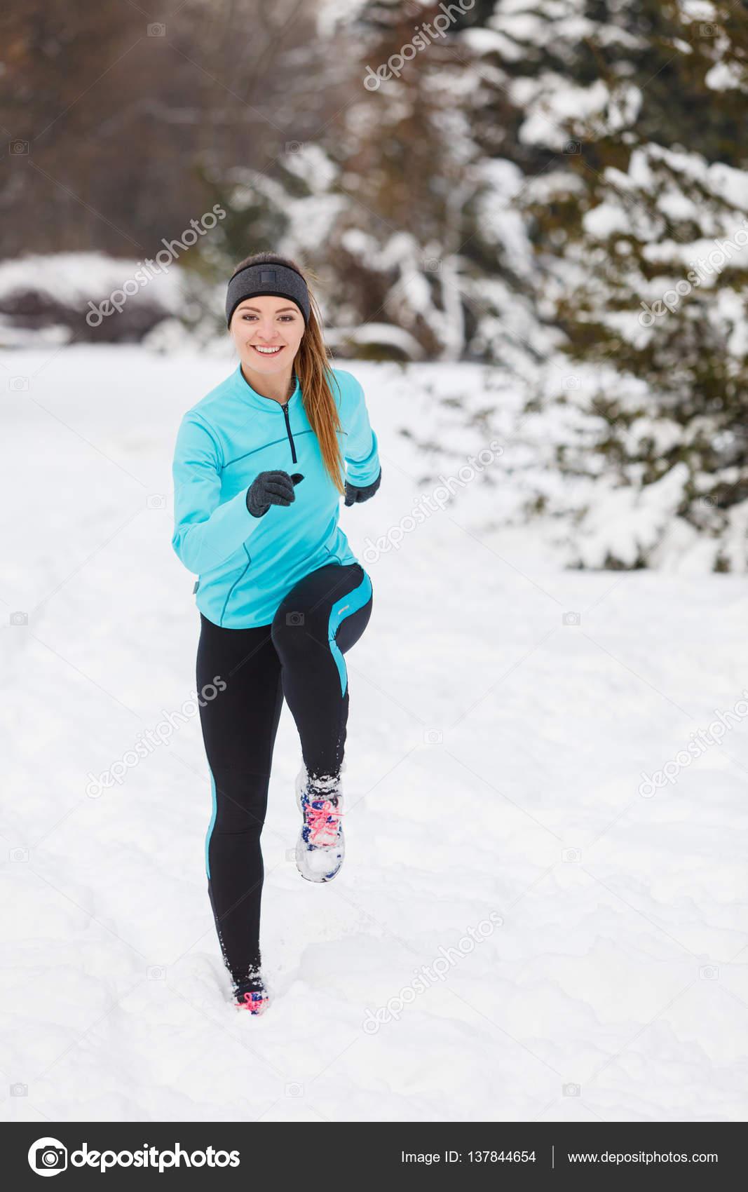 Дівчата носіння спортивний одяг і працює на сніг з дерев у фоновому режимі 7e0c108c69789