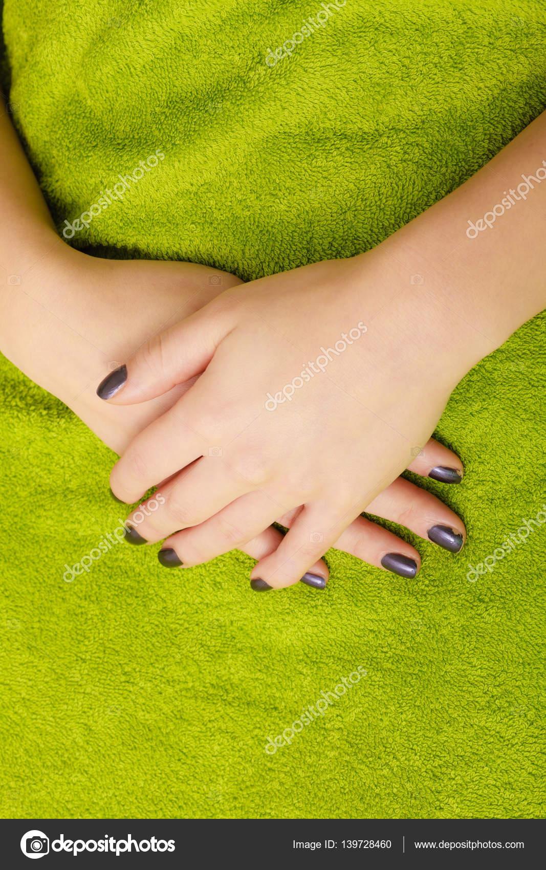 Manos de mujer con uñas oscuras sobre una toalla verde — Fotos de ...