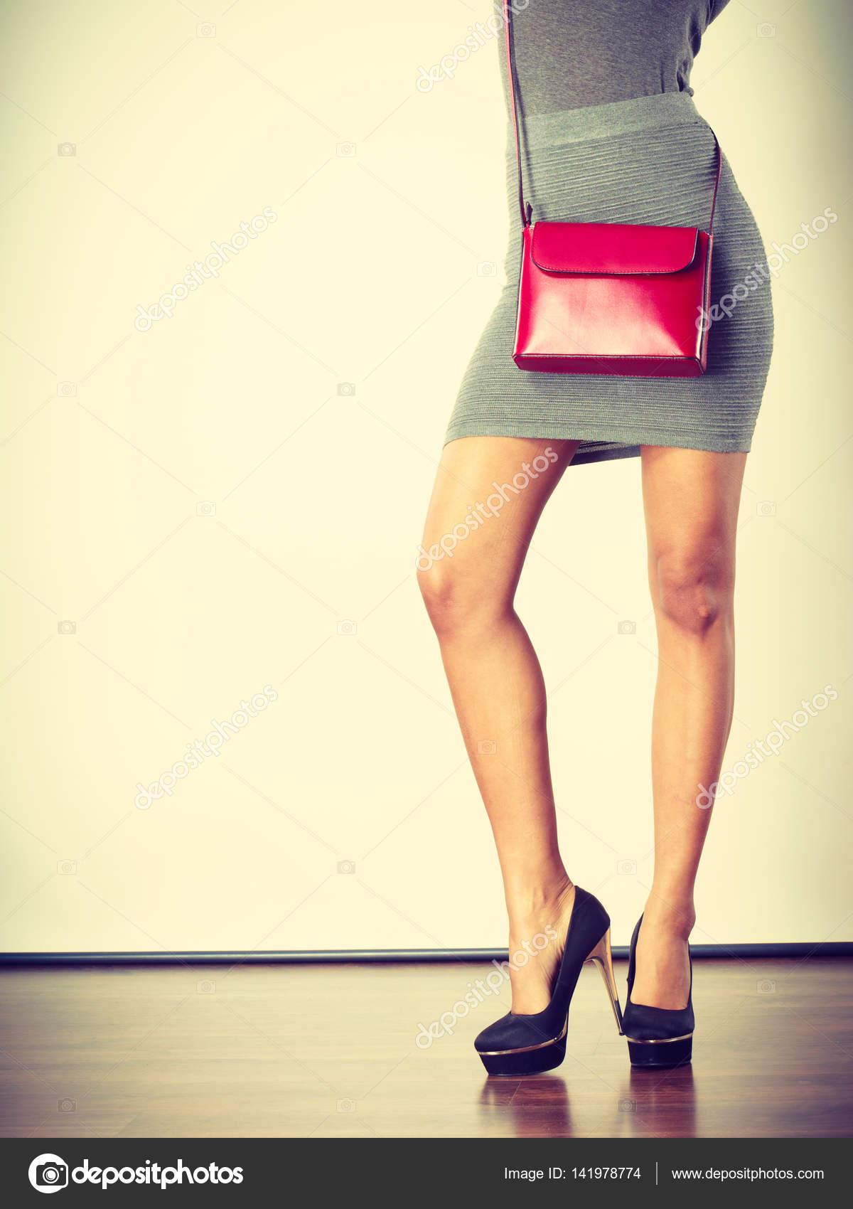 Jeune fille portant des chaussures talons hauts noir jupe courte gris avec  cuir rouge sac à main. Studio shot — Image de Voyagerix 16b91e1435d0