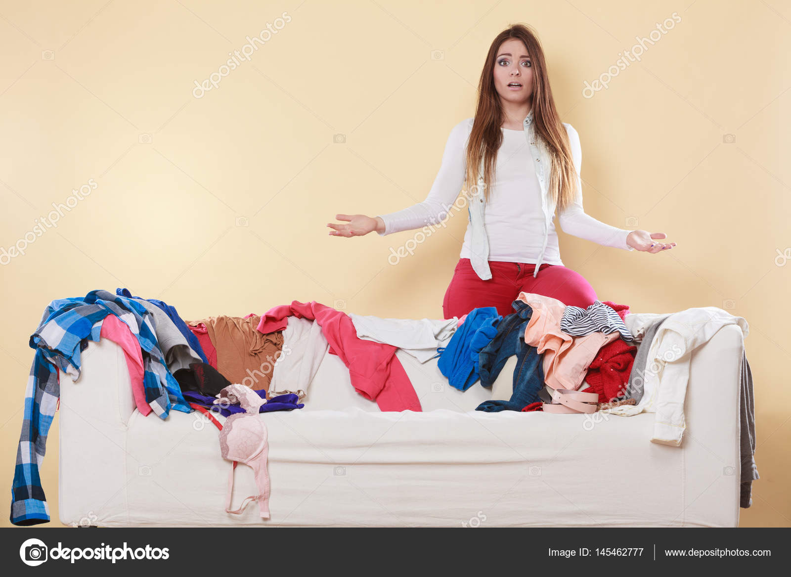 5e6b39624b Helpless woman standing behind on sofa couch in messy living room  shrugging. Young girl surrounded by many stack of clothes. Disorder and mess  at home.