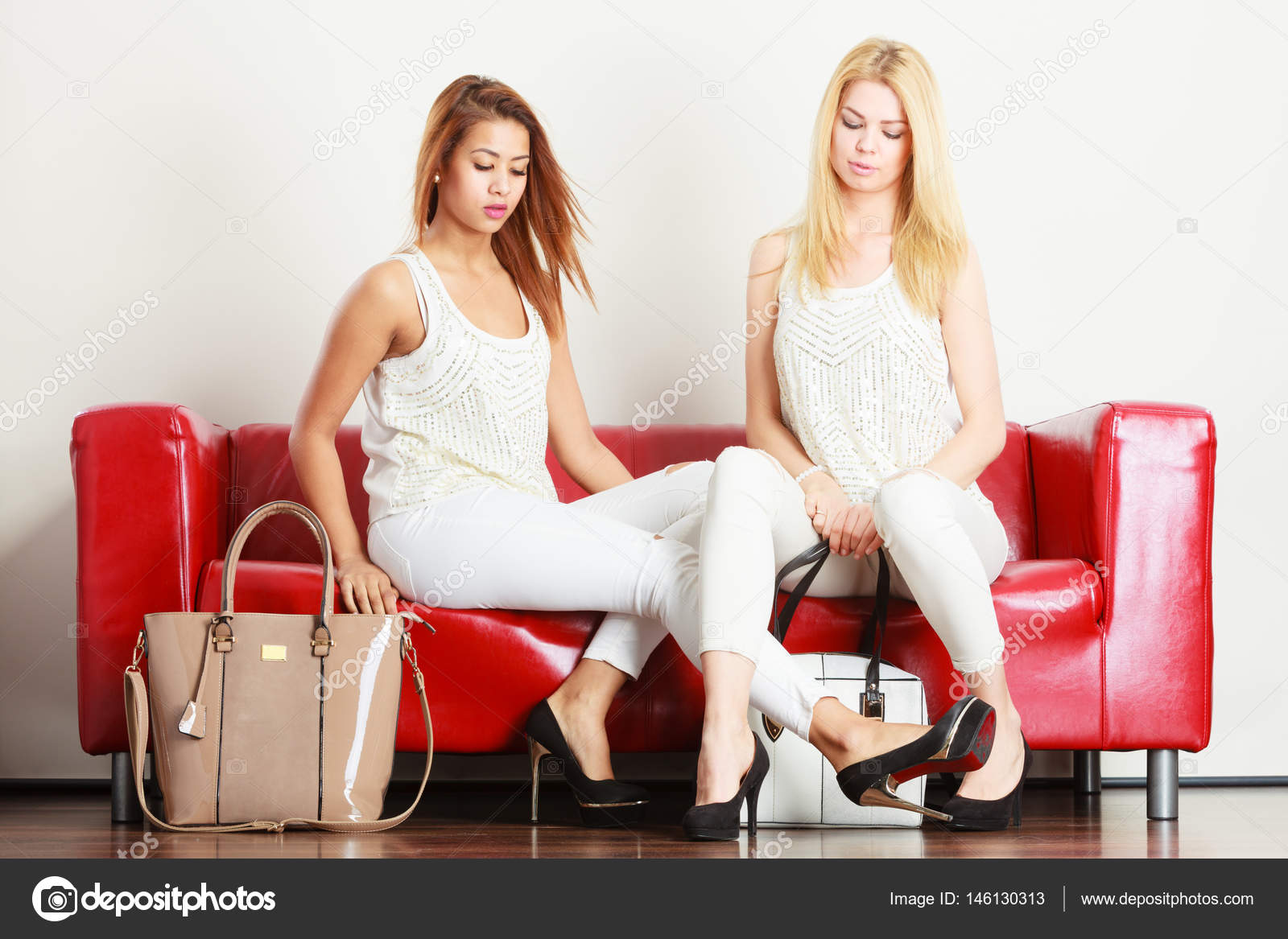 198f8b2a6 Két nő ül a kanapén bemutató táskák — Stock Fotó © Voyagerix #146130313