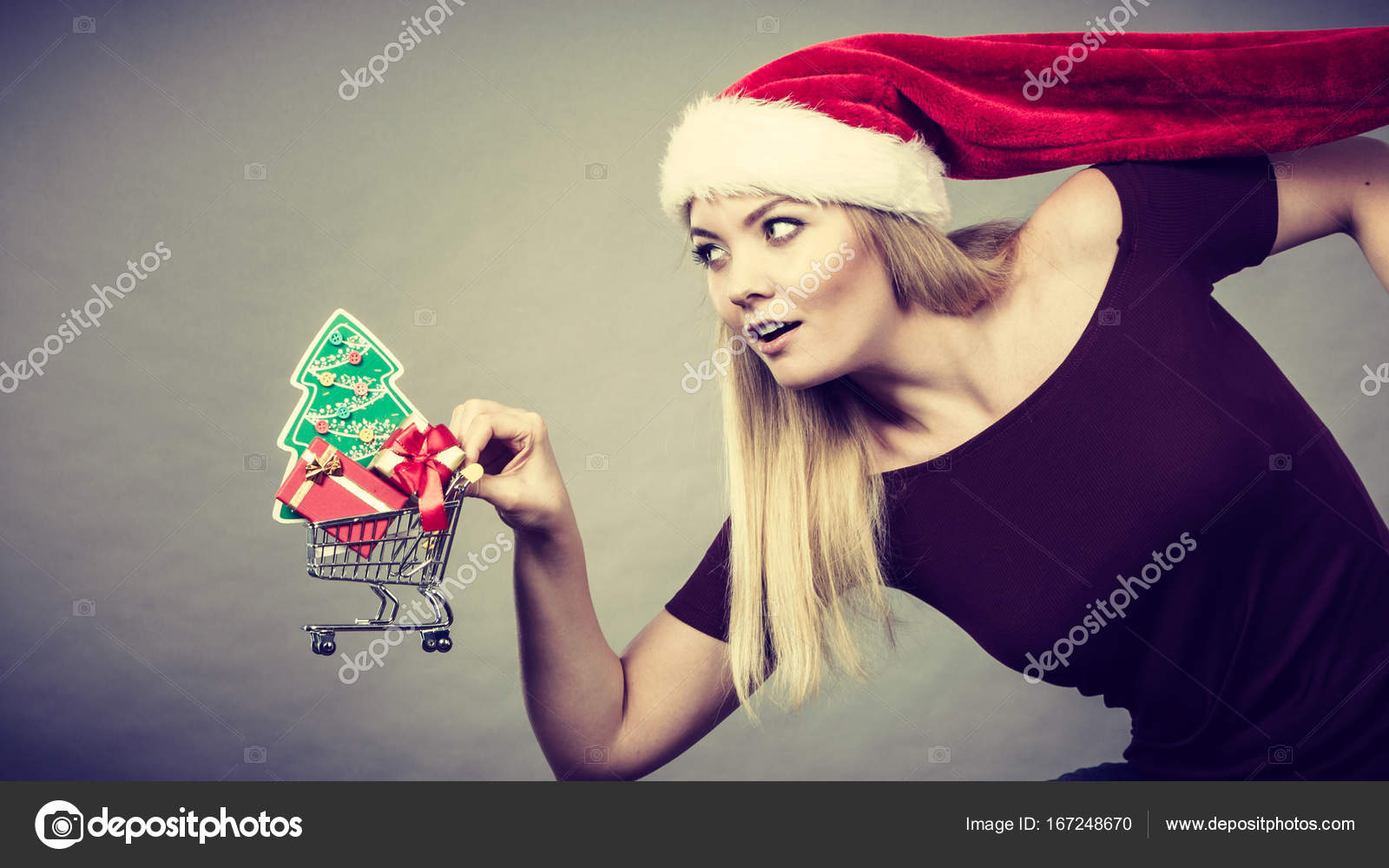 e6f3e1a7179a6 Happy woman wearing Santa Claus helper hat holding shopping basket cart  with little christmas tree and gifts inside running for sale. — Photo by  Voyagerix