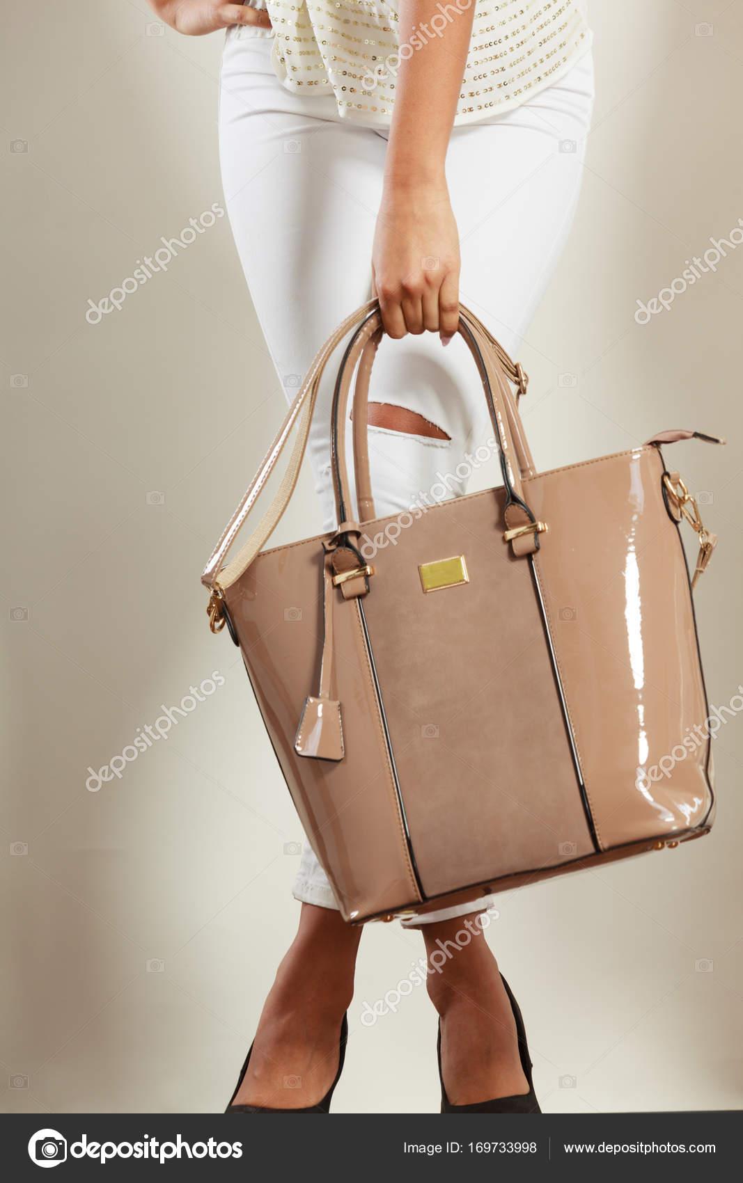 df82982267b5 Женщина, держащая бежевая кожа лаковая сумка– Стоковое изображение