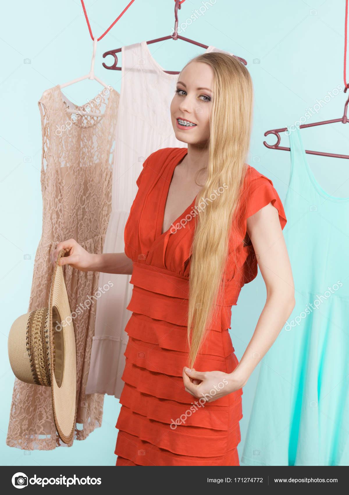 3e86112adb562 Femme dans la boutique de vêtements magasin tenue parfaite de la cueillette  l'été, tenant le chapeau à large bord, robe suspendus sur des cintres pour  ...