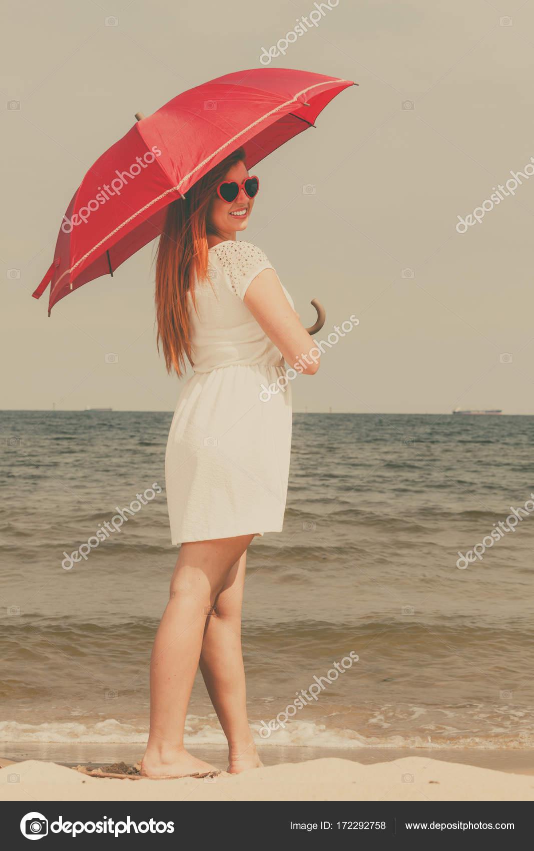 Rothaarige Frau Zu Fuss Am Strand Mit Sonnenschirm Stockfoto