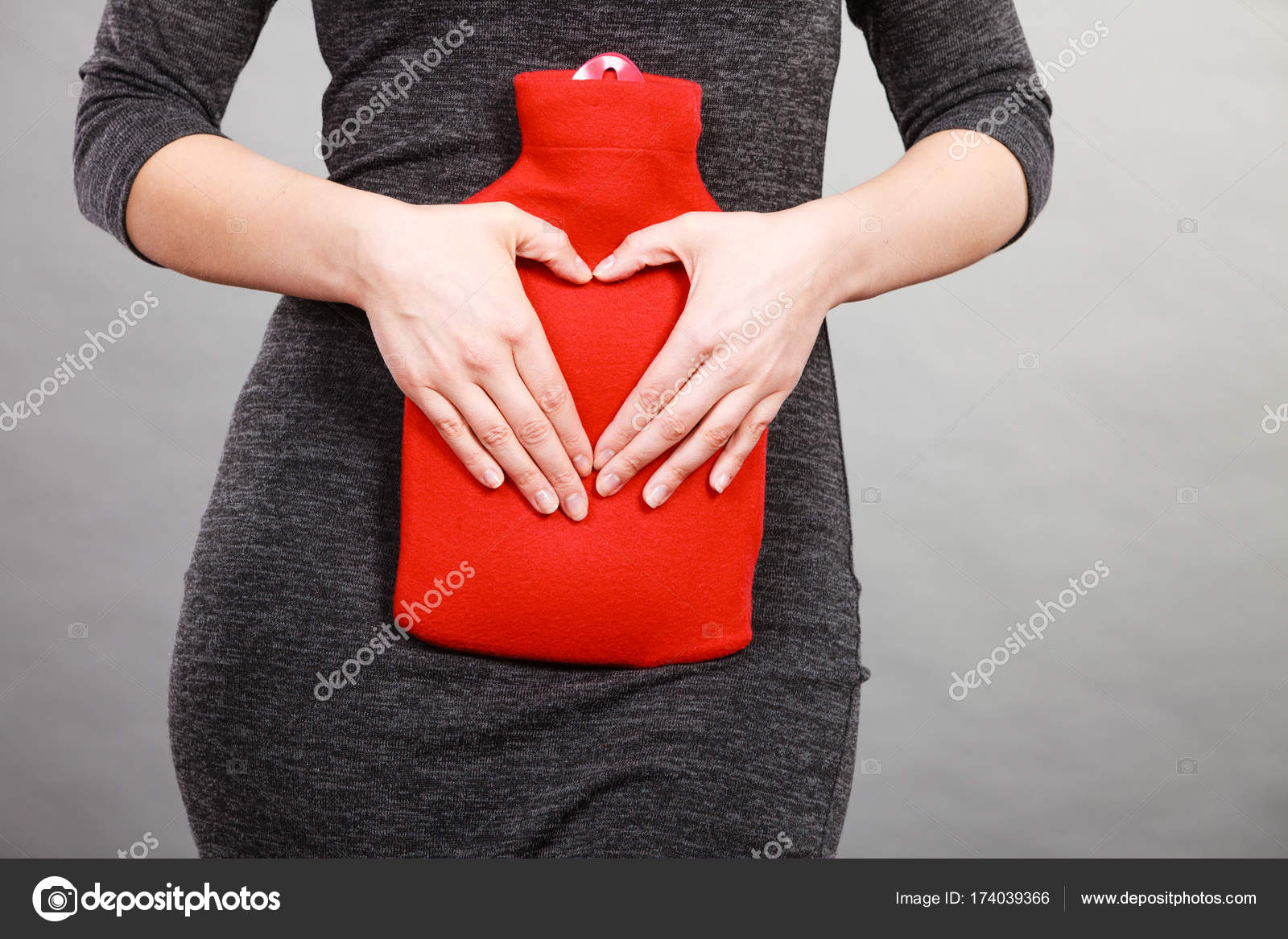 Girl holds hot water bottle on belly making heart shape by