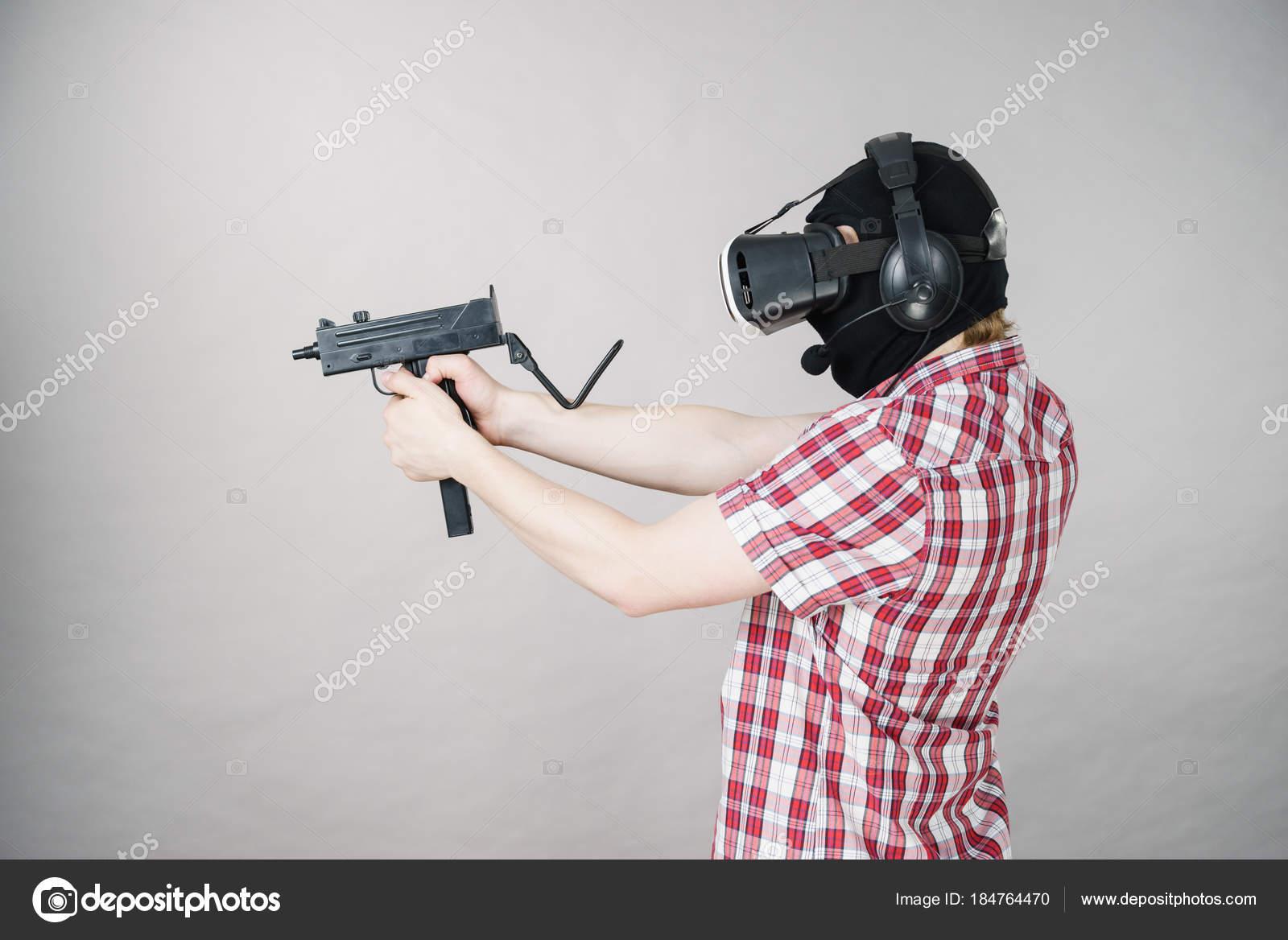 Gamer man wearing VR holding gun — Stock Photo © Voyagerix
