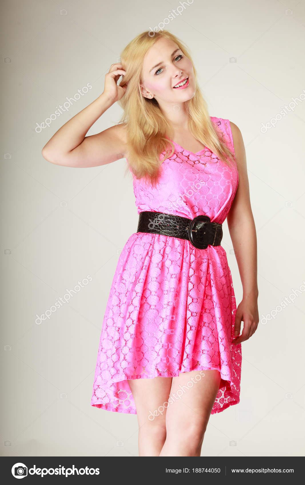 fd4eb3b84512 Όμορφη νεαρή γυναίκα που φοράει κοντό ροζ θηλυκό φόρεμα με μεγάλη μαύρη  ζώνη. Studio που γυρίστηκε σε λευκό φόντο — Εικόνα από ...