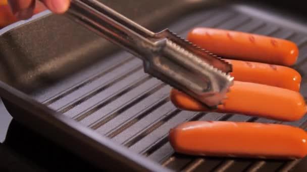 Video sklíčka grilování a odstranění klobásy na černé pánvi v kuchyni.