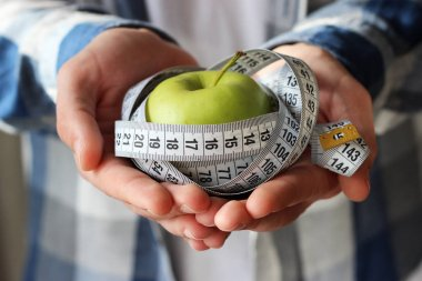 green apple and centimeter tape in male hands. diet, healthy, body, proper nutrition.