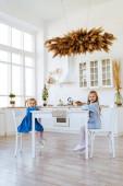 Két gyerek ül a konyhaasztalon..