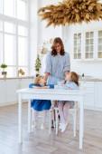 Anya a két gyerekével a konyhaasztalon ül..