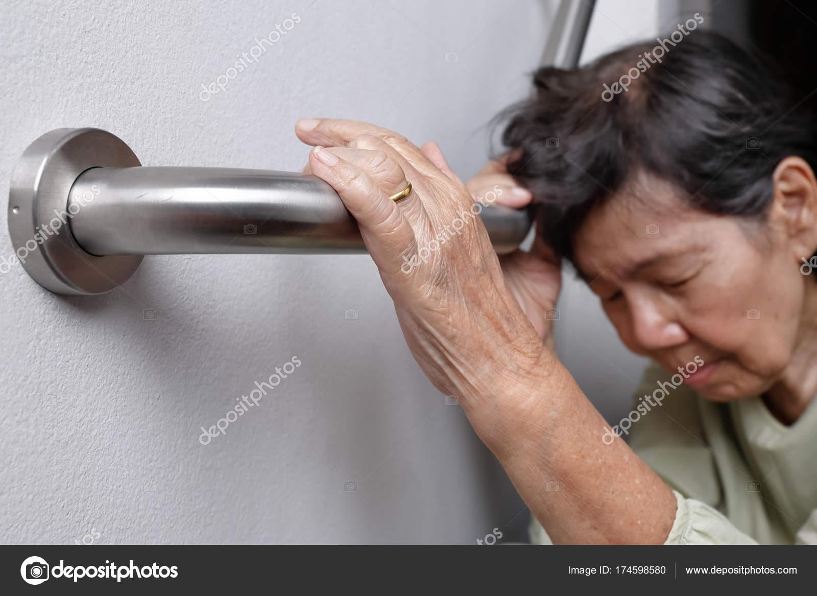 Elderly woman holding on handrail for safety walk steps — Stock ...