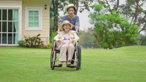 Donna anziana rilassarsi sulla sedia a rotelle nel cortile con la figlia