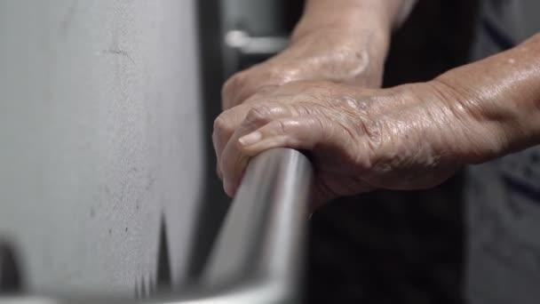 Mano donna anziana che tiene il corrimano per supporto a piedi