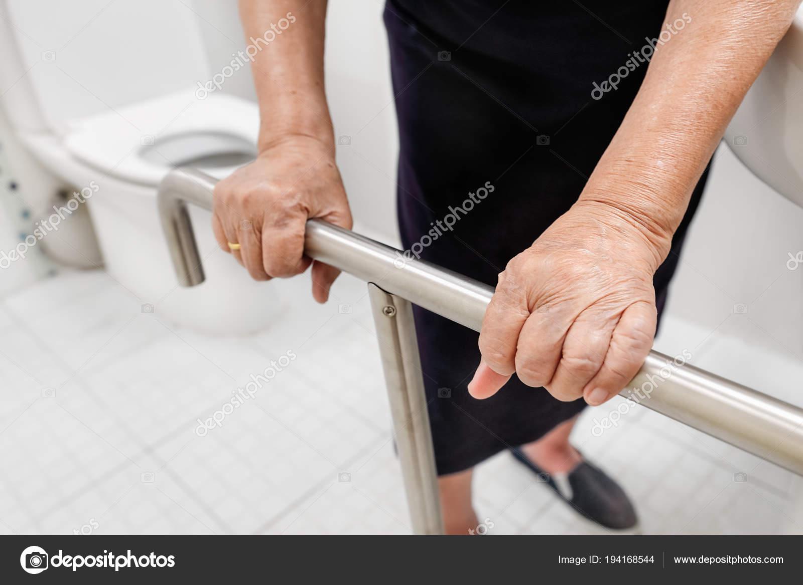 Elderly woman holding on handrail in toilet. — Stock Photo © toa55 ...