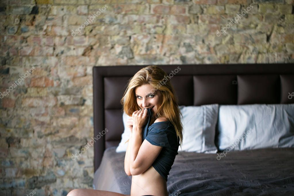 Sexy woman siting and smile on the bed at the morning
