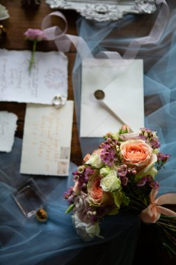Elegant wedding bouquet with ribbon, wedding invitation, rings on the wooden surface. Shooting from above