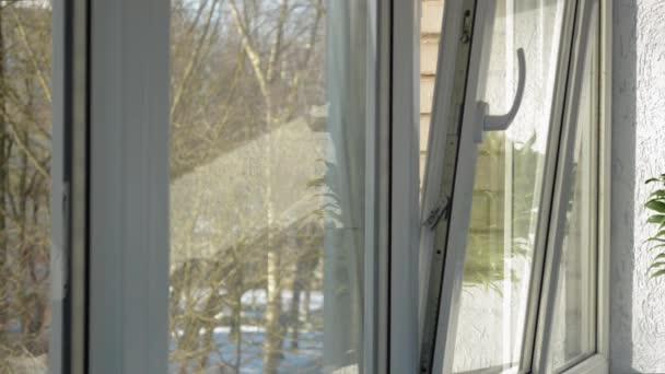 Plastové okno je otevřené a uzavřené mužské ruky