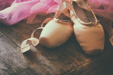 Image of silk pointe shoes and tutu on wooden floor
