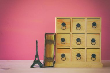 antique chest with drawers next to old book and eiffel tower