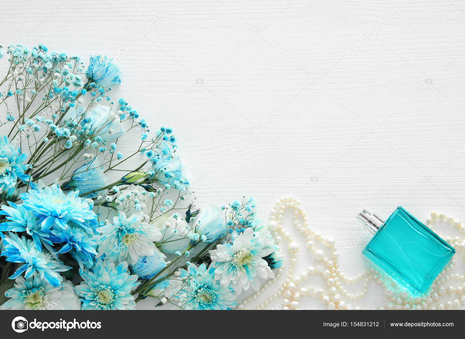 Beautiful and delicate blue flowers arrangement next to pearls beautiful and delicate blue flowers arrangement next to pearls necklace and fresh perfume stock photo izmirmasajfo