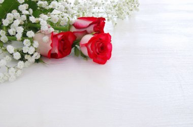 Top view of beautiful and delicate roses on wooden background
