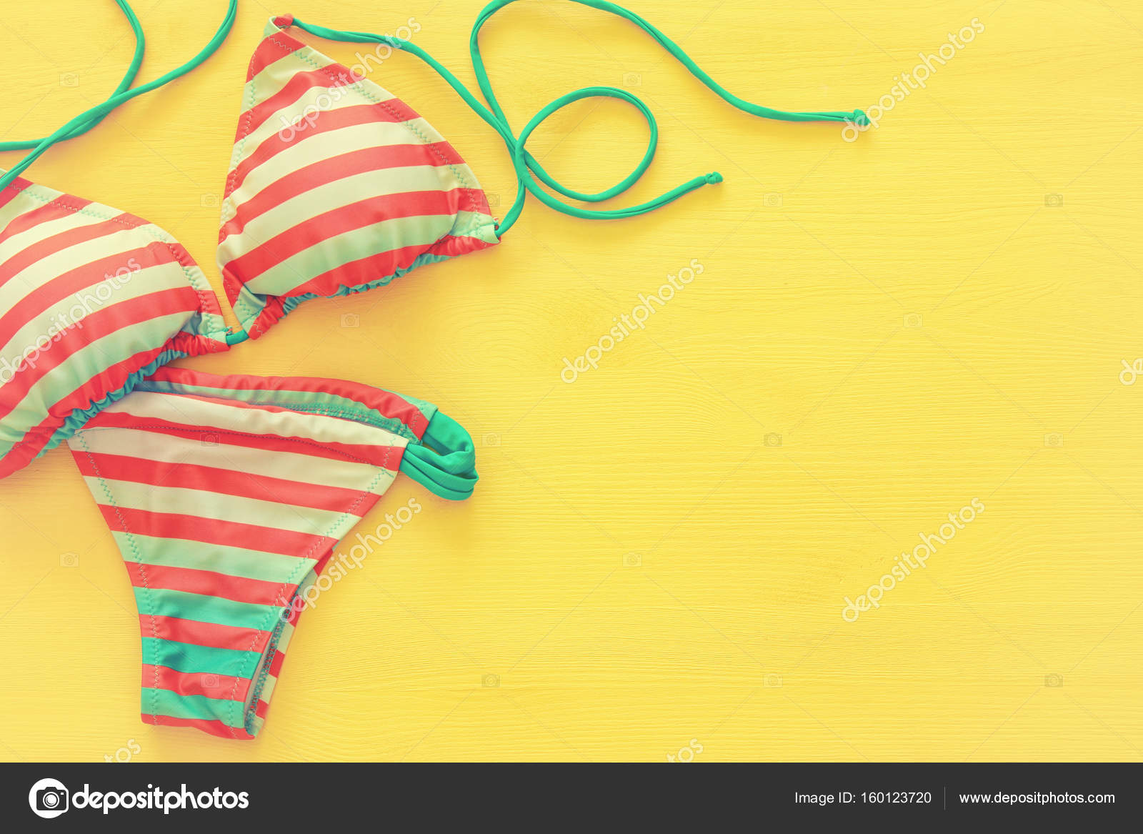 052d9c3ef2 Top view of fashion female swimsuit bikini on yellow wooden background.  Summer beach vacation concept — Photo by ...