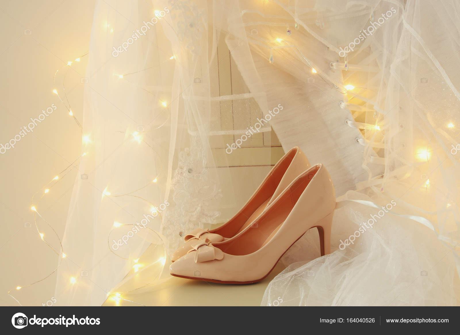 Schöne weiße Hochzeitskleid und Schleier auf Stuhl mit gold Girlande ...