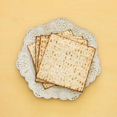 passover background with matzoh over yellow wooden background.