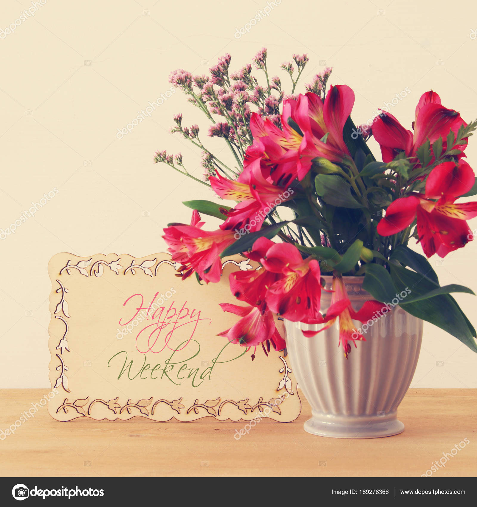 summer bouquet of red flowers in the vase over wooden table and ...