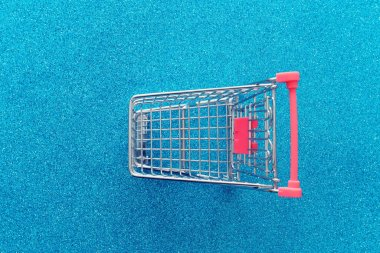 Image of shopping cart over blue glitter background. View from above