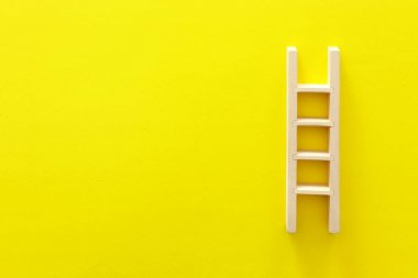wooden ladder over yellow background