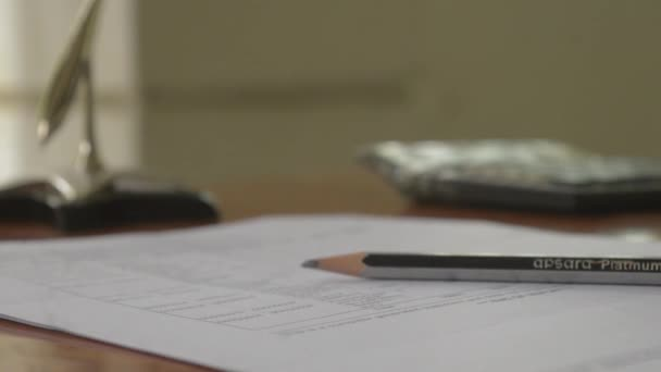 Close up of pencil on the desk. Calculator, paper, document, note pad in the background. Business, finance, tax, investment, report, paperwork, background concept.
