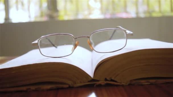 Otevřená kniha a brýle nebo brýle na dřevěném stole, v teplém slunečném ránu, boční pohled zblízka. Nedělní prázdniny. Izolované pozadí ve selektivním zaměření s mělkou hloubkou pole.