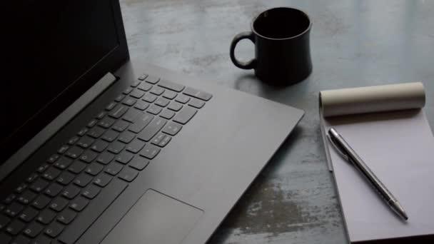 Reggeli kávé reggeli napfény laptop számítógép fekete színű toll és fehér papíralapú notebook, kerámia csésze felső irodai munka asztal rozsdaszínű felületi háttér. Életmódkép.