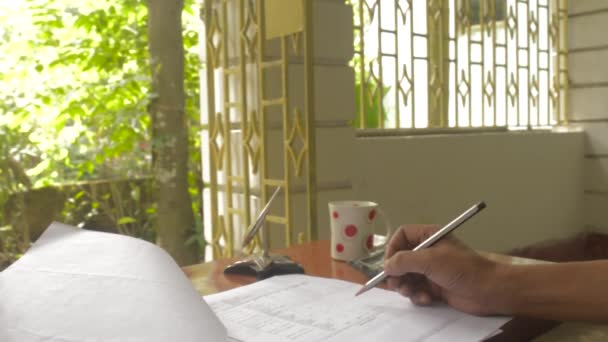 Woman hand doing calculation on a white sheet of paper using calculator. Indian paper currencies and documents on finance accounting table. Calculation of home finance, accounting costs, Debt, Household expenses concepts.
