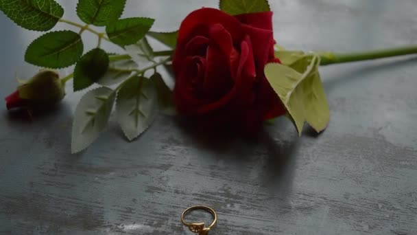 Close up gold engagement ring jewelry on rustic metal floor. Soft focus romantic Red rose flower in background. Love Proposal or Propose concept for valentines day wedding and holidays. Copy Space.